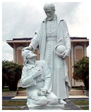 Statue of priest blessing a parishner.