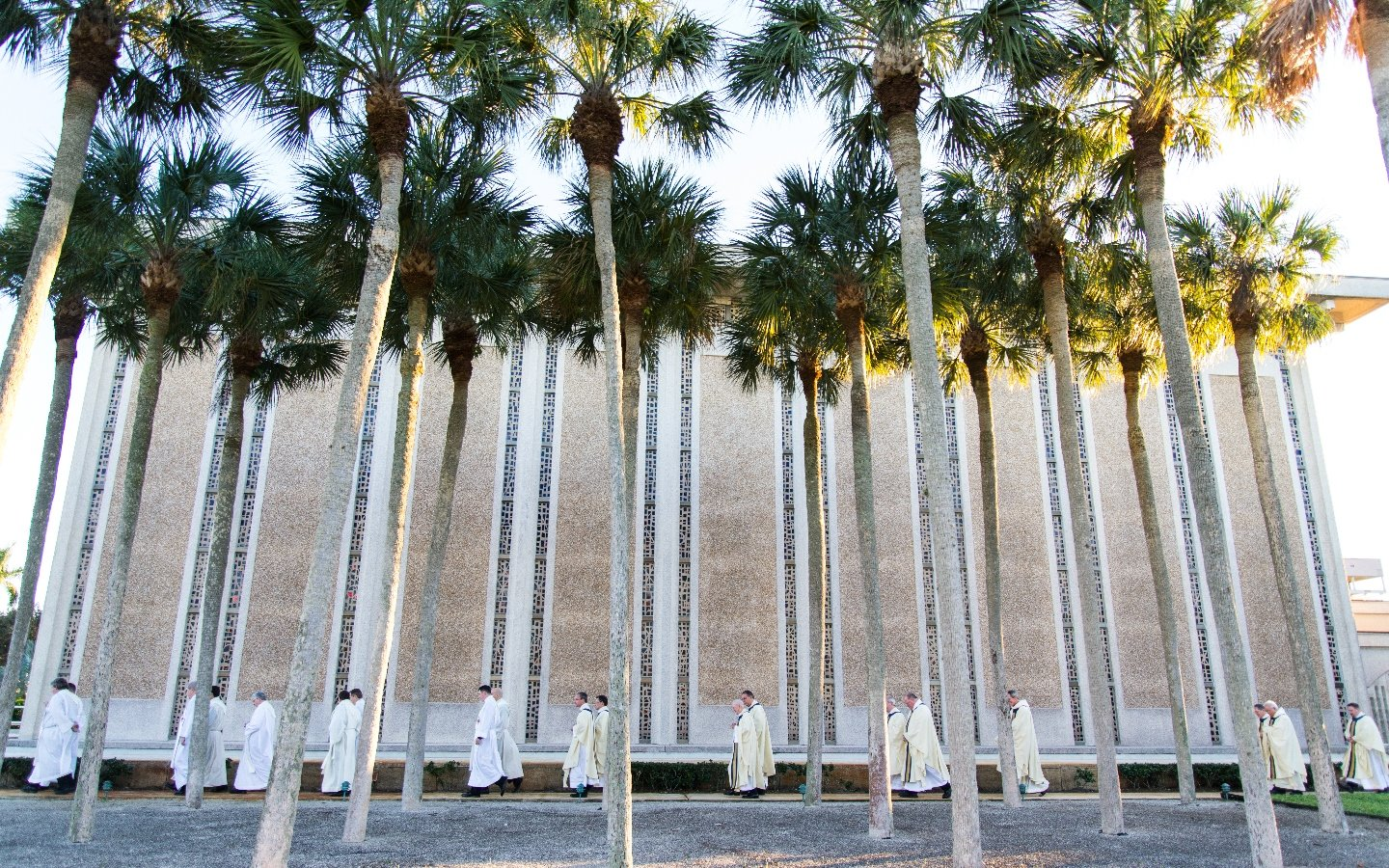 Priests walking in front of chapel and palm trees
