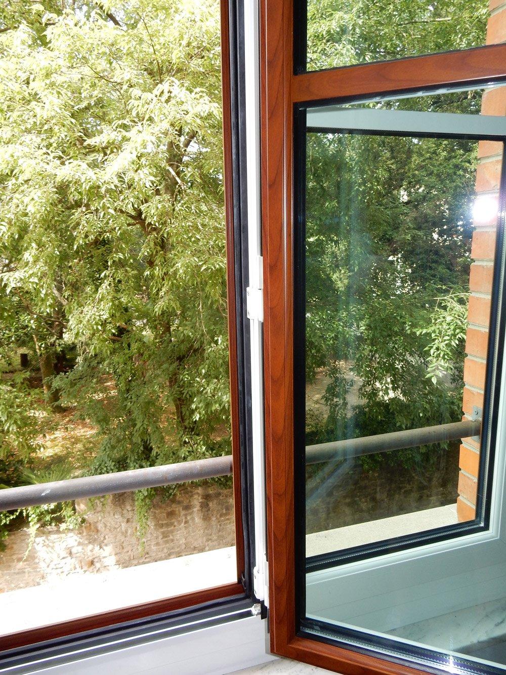 particolare di una finestra aperta con vista su degli alberi