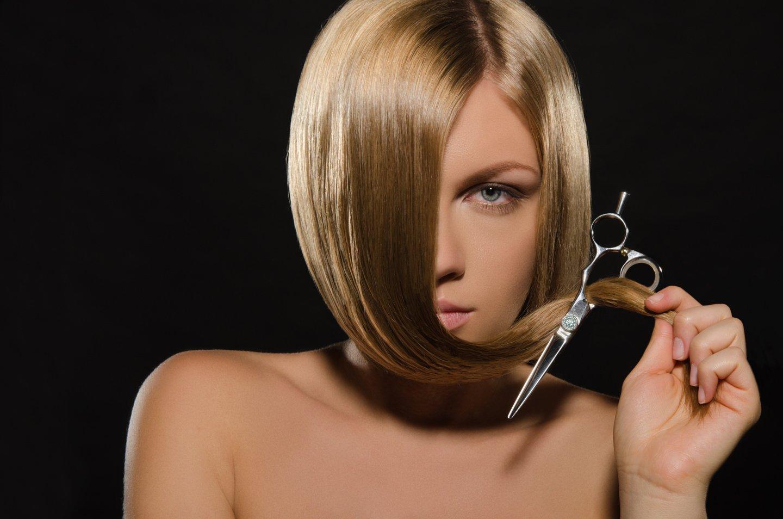 una modella con capelli bionda tiene un forbice in mano