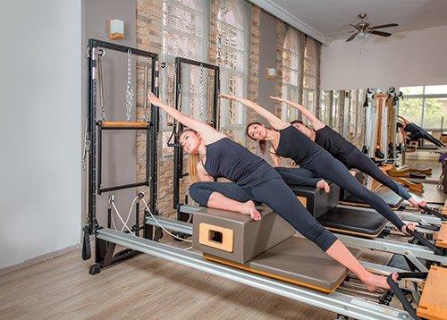 ragazze eseguono esercizio di pilates con attrezzo