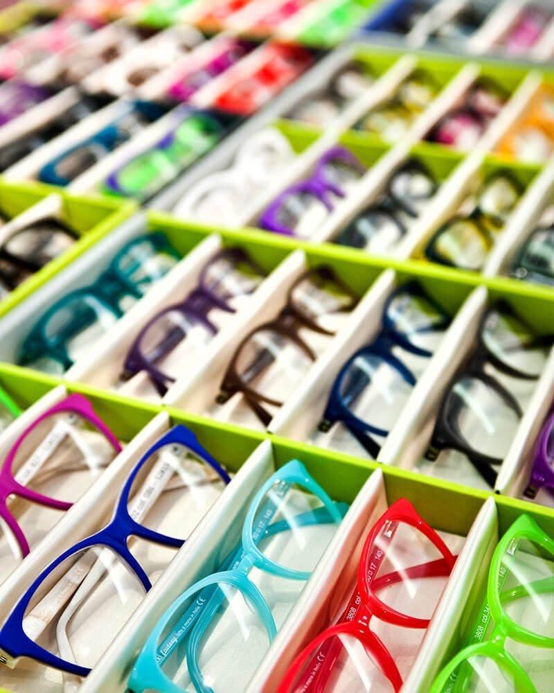 Vista laterale di un cassetto pieno di occhiali da vista colorati.