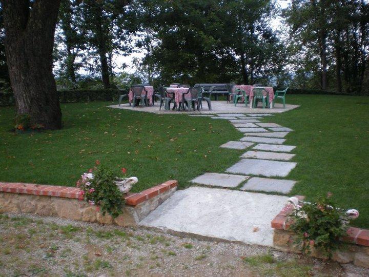 sentiero che porta a dei tavolini apparecchiati in mezzo a un giardino