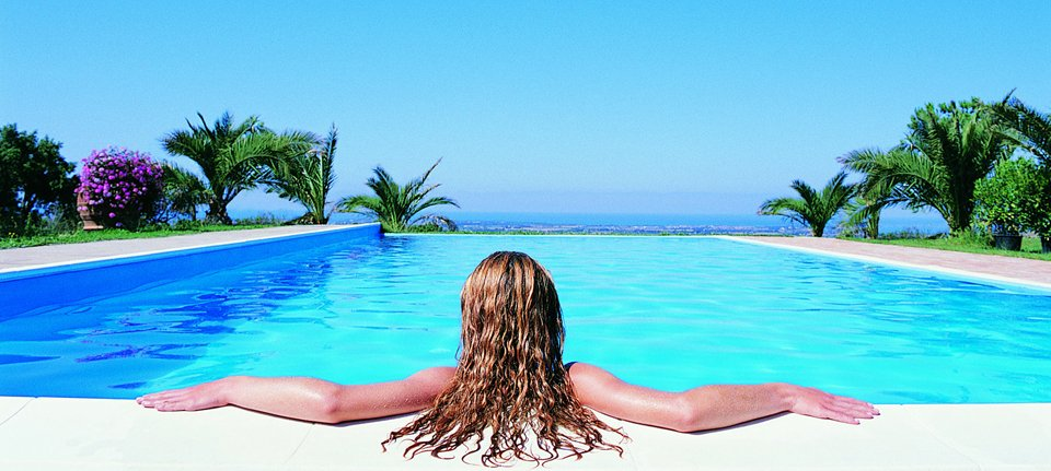 woman seen from behind in infinity swimming pool