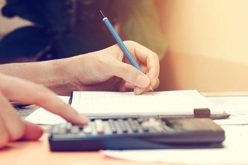 calcolatrice per elaborazione dati fiscali sopra un tavolo in legno con mano che scrive su un foglio con una penna