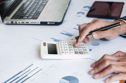 mani su un tavolo con penna e calcolatrice