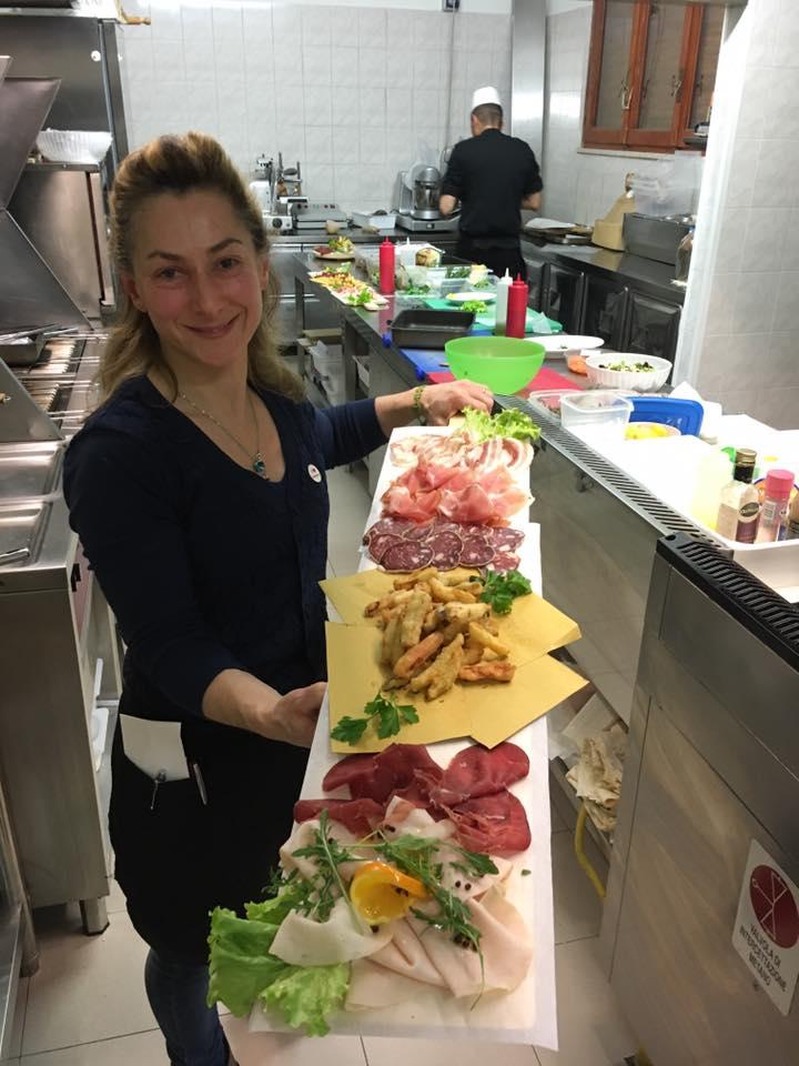 una donna in cucina con un tagliere di salumi e delle verdure in pastella