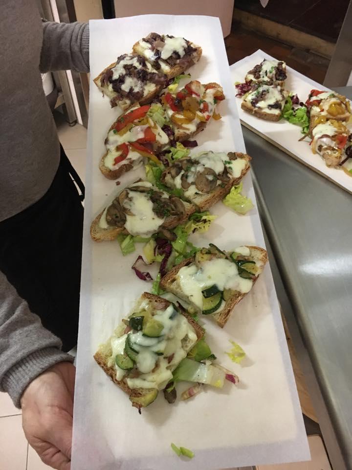 un tagliere di fette di pane farciti con le verdure e formaggio