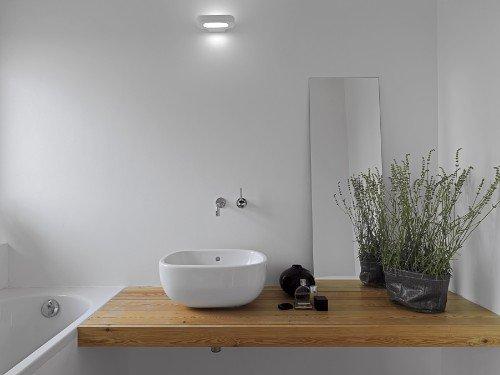 vasca, lavabo tondo e mensola in legno in un bagno