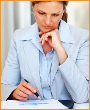 Woman in a blue suit, with her hand on her chin, looking at paperwork