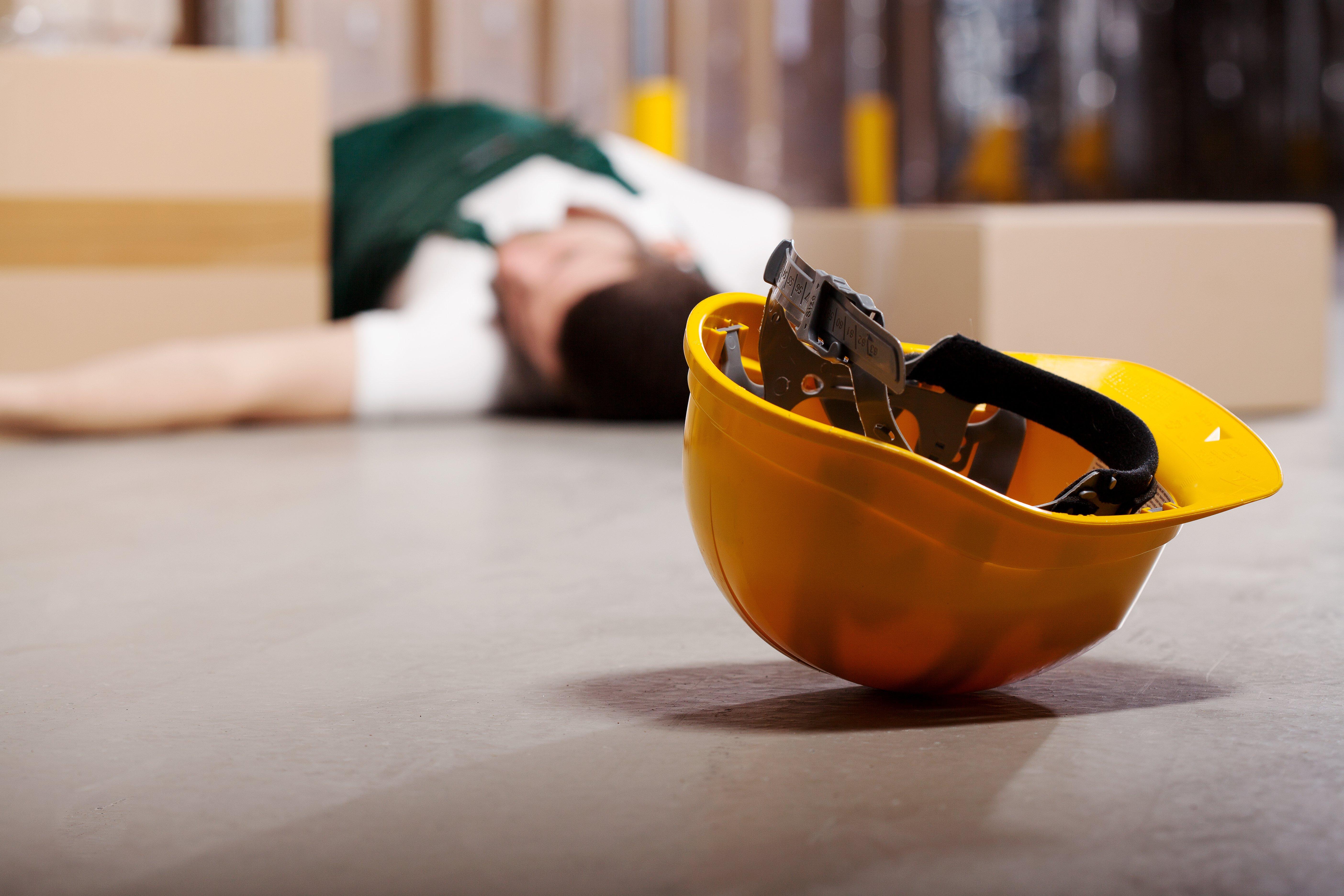 An injured worker lies on the ground