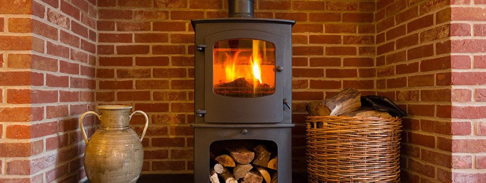 A wood burning stove in a recessed brick fireplace