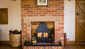 A brick firepalce and chimney breast with a log burner in it