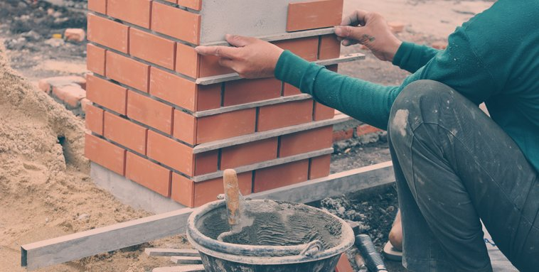 A person laying bricks