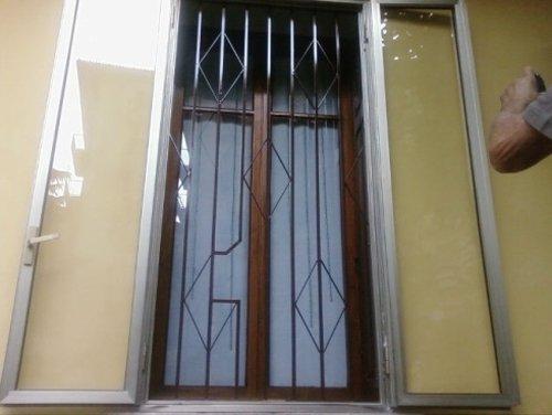 finestra con inferriata e parete gialla di una casa