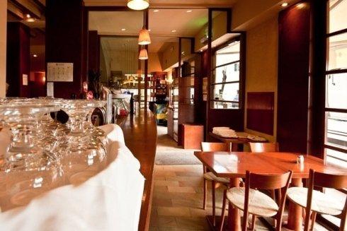 interno di un ristorante con sulla sinistra un bancone con una tovaglia bianca con dei bicchieri appoggiati e sulla destra i tavoli