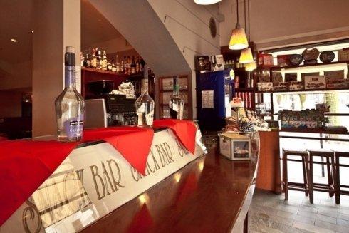 vista del bancone del bar con una tovaglia rossa  e sopra delle bottiglie di alcolici