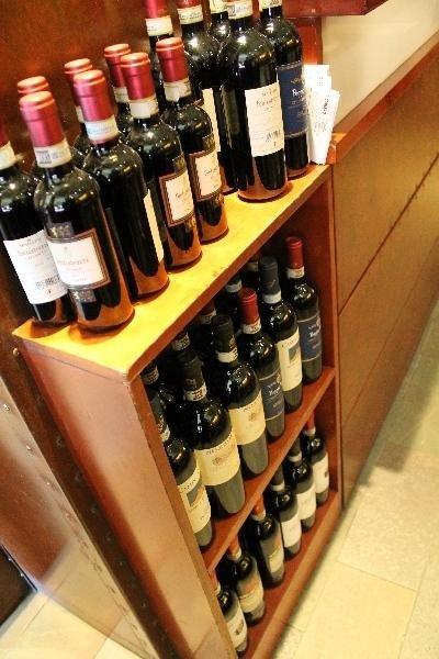 dei vini in esposizione sopra e negli scompartimenti di un mobiletto marrone