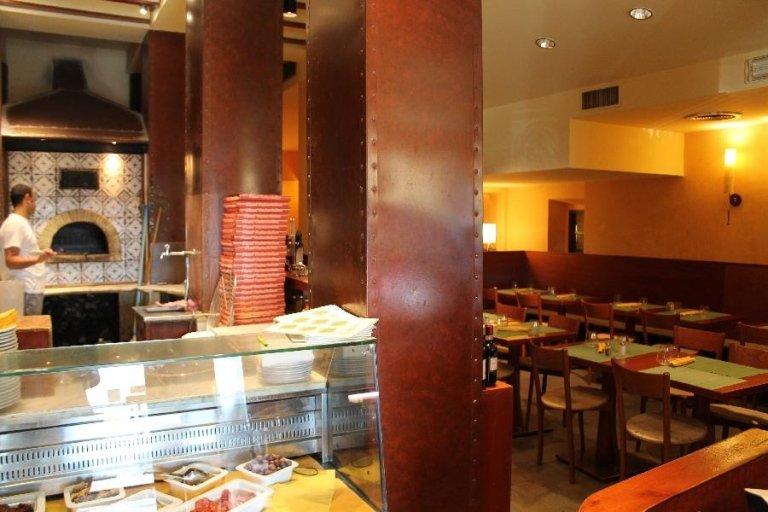una vetrina vicino al bancone con dentro del cibo nei contenitori, dietro un pizzaiolo vicino al forno e sulla destra i tavoli