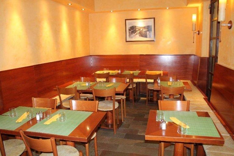 la saletta da pranzo con i tavoli apparecchiati con delle tovagliette e un quadro appeso al muro
