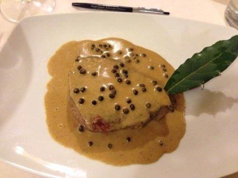 Un piatto di carne con una salsa gialla al pepe verde e una foglia di alloro