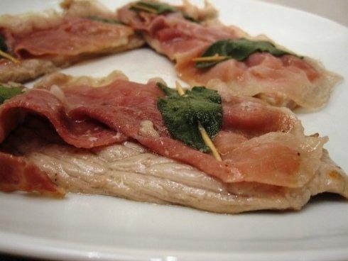 Un piatto con dei petti di pollo,salumi e delle foglie di salvia