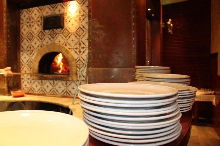 Dei piatti bianchi appoggiati su un banco e vista del forno sul lato sinistro