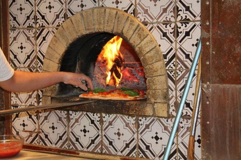 Un pizzaiolo mentre sforna una pizza dal forno a legna