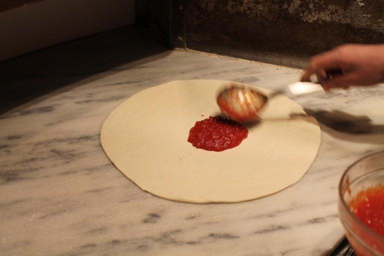 Una mano mentre versa il sugo su una pizza con un cucchiaio