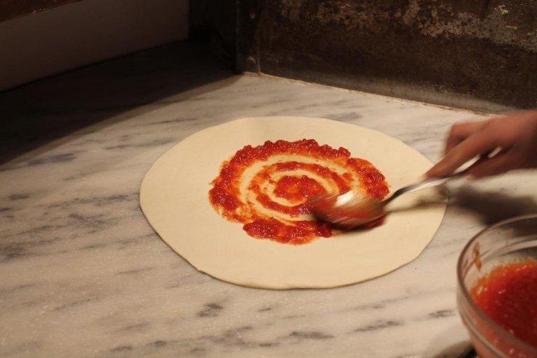 Una pizza con del sugo appoggiato su un marmo