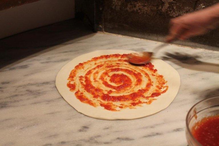 Una pizza con sugo di pomodoro pronta per essere infornata
