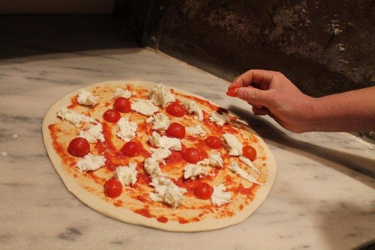 Una pizza con sugo, mozzarella e pomodorini