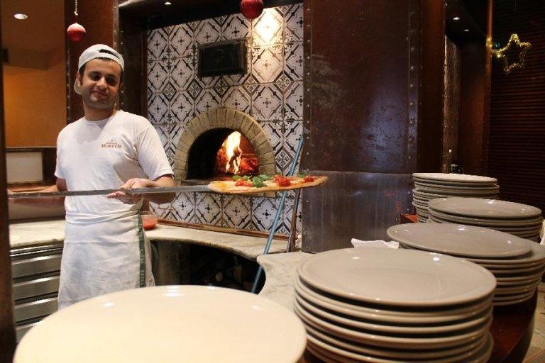 Un pizzaiolo mentre appoggia la pizza su un piatto con una pala da forno