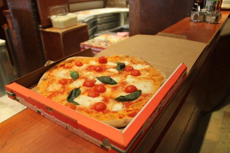 Una scatola con dentro una pizza margherita con pomodorini