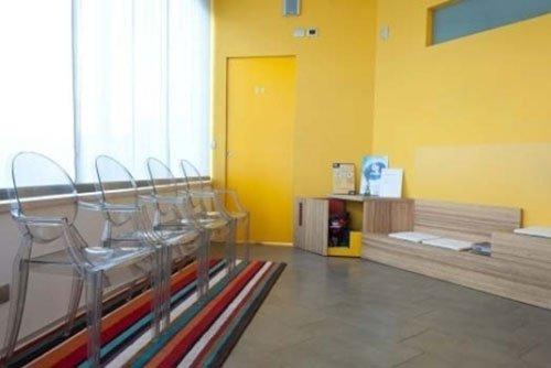 Sala d'attesa, pareti gialle e pavimento di legno