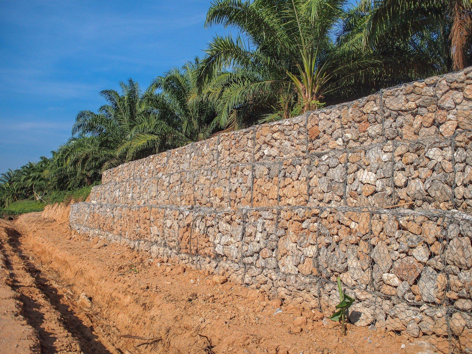 una rete metallica davanti a un muretto in pietra e vista delle palme