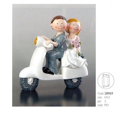 torta a forma di due sposi su una mota bianca
