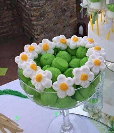 coppa con caramelle verdi e contorno di margherite