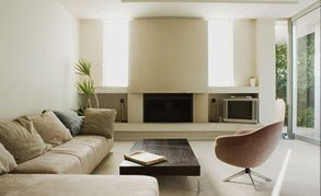 Cream leather sofas and coffee tale in front of a large fireplace and TV viewing area