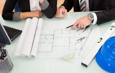 A man and woman sitting at a white table looking at building plans