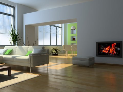 A burning fireplace set into a white wall in a long room with alcove and wooden floors