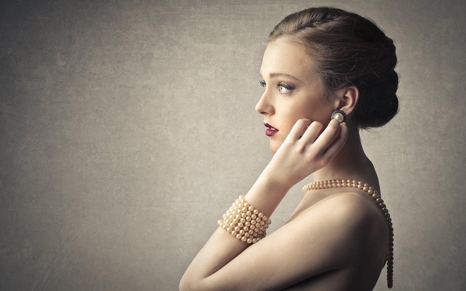 una donna con un bracciale e una collana di perle