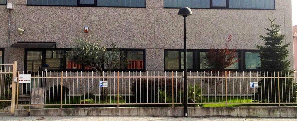 Vista dall'esterno di uno stabile con telecamera sopra alla  porta d'entrata,  una ringhiera con un cancello e un segno adiacente con scritto Rimola S.r.l