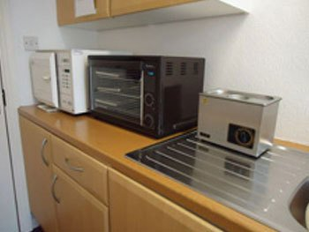 Kitchen with wooden units, chrome draining board and black microwave