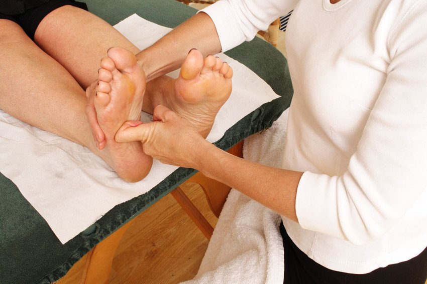 A therapist working on the soles of a patient's feet