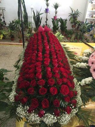 una corona di rose rosse su una bara