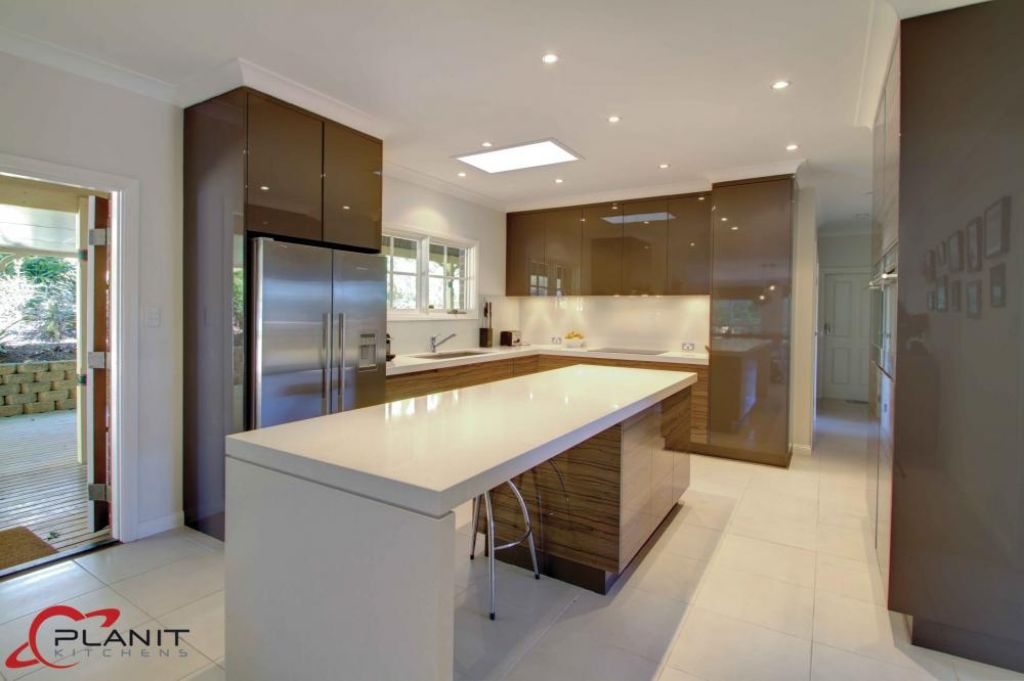 contemporary wood panelled kitchen with island and breakfast bar
