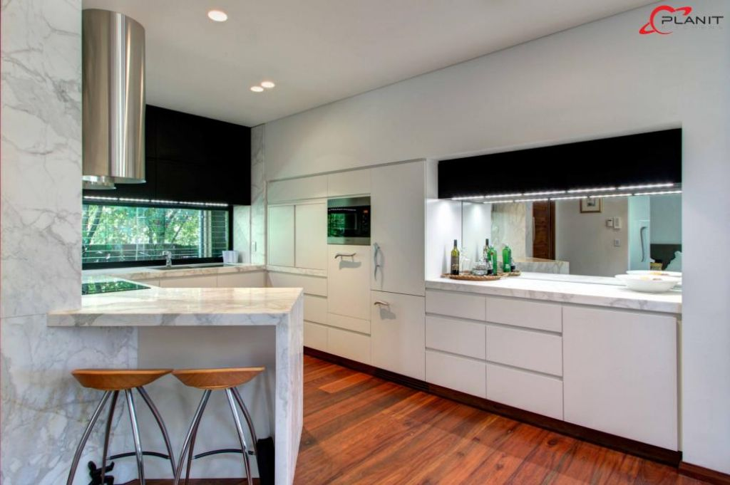 elegant marble featured kitchen with small breakfast bar