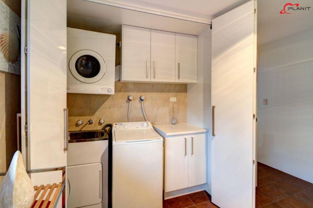 classic laundry hidden by cupboard doors open