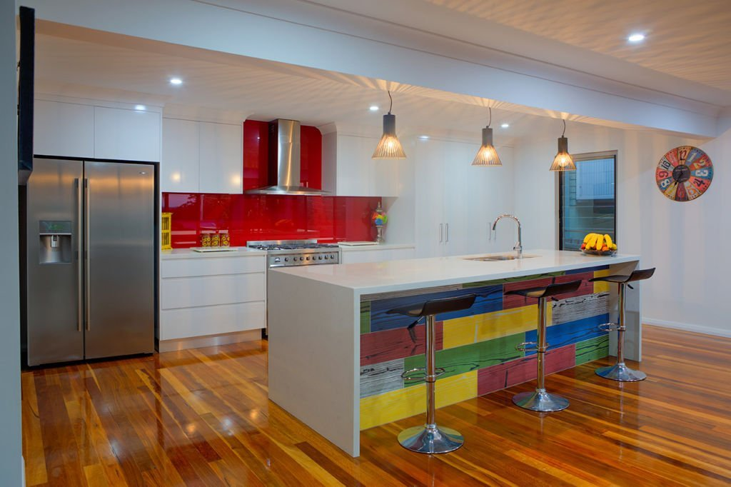 contemporary kitchen with multicolour feature island with red splashback